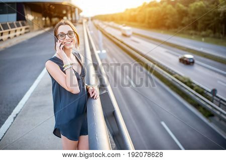 Portrait of a young businesswoman talking with phone on the highway during the business trip on the sunset
