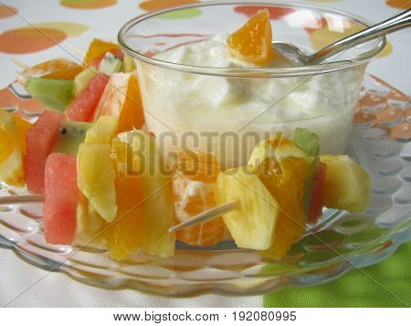 Fruit spears with melon, orange, pineapple and yogurt