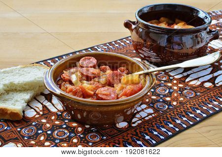 Vegetable stew in bowl and ceramic pot over colorful table cloth