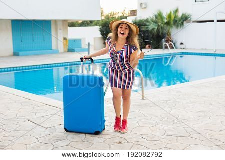 Happy young woman with blue luggage arriving to the resort. She is walking next to the swimming pool. Beginning of summer vacation concept