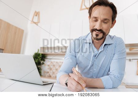 Immersed into work. Cheerful young man sitting behind the kitchen counter, holding a pencil and making notes while smiling and looking pleased