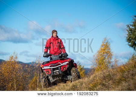 Bottom View. A Guy On The Red Atv Quad Bike Against Blue Sky In The Autumn Landscape Nature. Sunny D