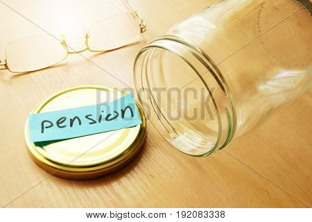 Empty jar with label pension. Retirement saving troubles concept.