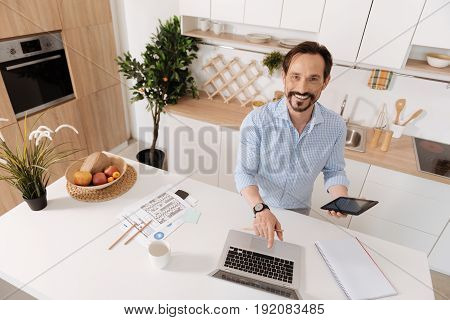 Content with work. Young bearded man standing near the kitchen counter, holding a tablet and pointing at his laptop while looking at the camera and smiling
