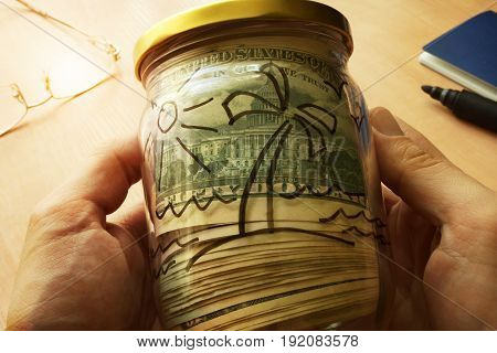 Jar with dollars and picture of island on a side. Money for traveling and vacation.