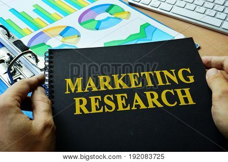Documents with title marketing research on a table.