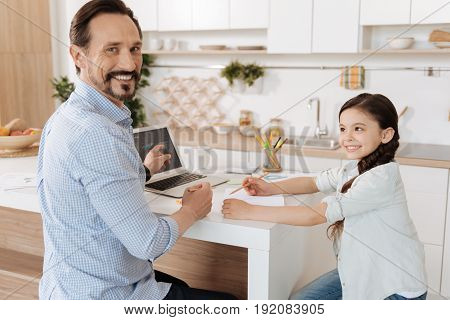 Happy to help. Lovely little girl sitting at the kitchen counter and looking at her young father while he pointing at the laptop with his finger and looking at the camera with a smile.