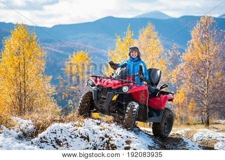 Smiling Woman In Blue Jacket Riding A Red Quadbike On Snow-covered Hill At Sunny Day Against Trees W