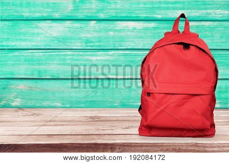 Red wooden surface backpack back to school green objects