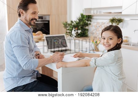 Positive mood. Pleasant young father sitting at the kitchen counter, holding a pencil and being ready to help his cute daughter with her home assignment while she looking at the camera and smiling