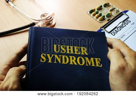 Hands holding book Usher syndrome. Medical concept.
