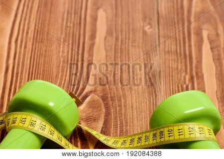 Dumbbells Of Green Colour And Yellow Sewing Centimeter