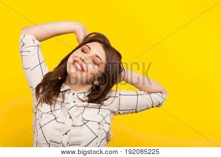 Young girl in shirt stretching with eyes closed looking dreamy on yellow.