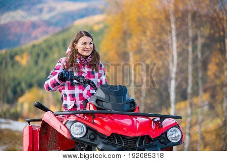 Close-up Portait Of Happy Girl In Winter Clothing On Red Quad Bike In The Autumn Nature