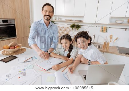 Math with pleasure. Lovely single-parent family sitting at the kitchen counter and doing math home assignment together with young father using a compass and his children looking at the camera