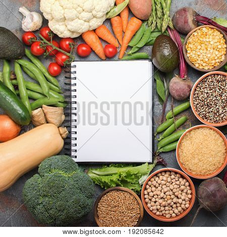 Different vegetables and grains, arranged in a circle with white notebook in the middle, broccoli, squash, beans, tomatoes, carrots, avocado, top view, square, selective focus