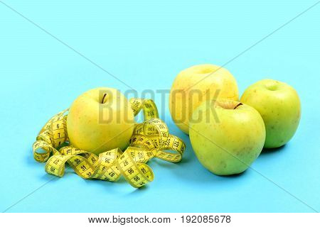 Apples In Green Color And Yellow Tape For Measuring