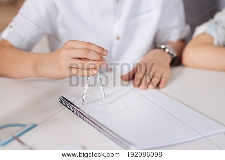 Moment of creation. The close up of delicate neat hands of a boy sitting at the table, holding a pair of compasses and inscribing circles