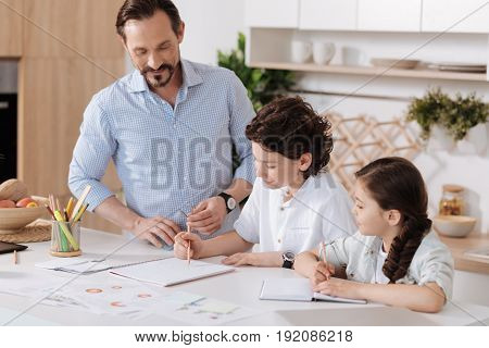 Proud of children. Handsome young father watching his intelligent little son doing sums in the notebook while his lovely daughter making notes