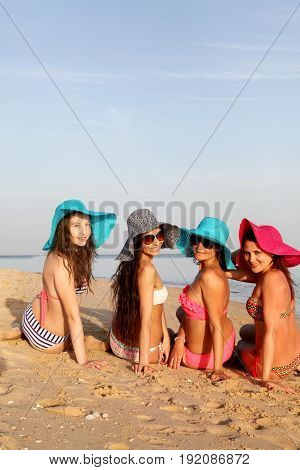 Beautiful slender young girls in bathing suits, hats and sunglasses are sitting with their backs and smiling at the camera on the beach