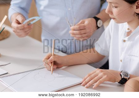 Focused on assignment. The close up of a cute little schoolboy drawing circles with a pencil while his father standing next to him and being ready to hand him a protractor and a pair of compasses