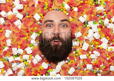 Young man with beard lying in sweets and candies looking at camera with amazement.
