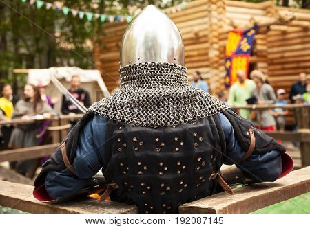 Middle ages period costume at knight tournament. Medieval historical reenactment - a man wearing metal helmet with aventail back view
