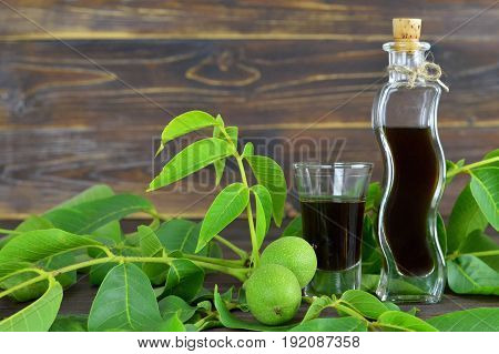Close up of walnut liqueur on wooden background
