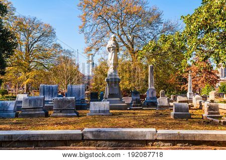 Atlanta, Georgia, USA - December 22, 2016:Group of tombstones and sculpture of Virgin Mary on the Oakland Cemetery in sunny autumn day