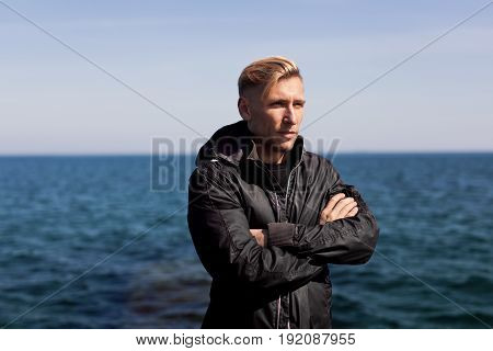 Young man wearing black windbreaker and posing with hands crossed looking away on background of sea.