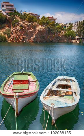 Old fishing boats in harbor of Agios Nikolaos, Crete, Greece. Vertical image