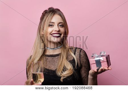 Young stylish woman holding wineglass with champagne and small giftbox on pink background.