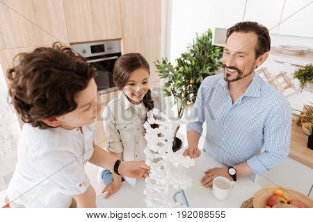 Discovering together. Cheerful close-knit family standing around a big 3D DNA model, scrutinizing it while looking inspired and pleased to study together