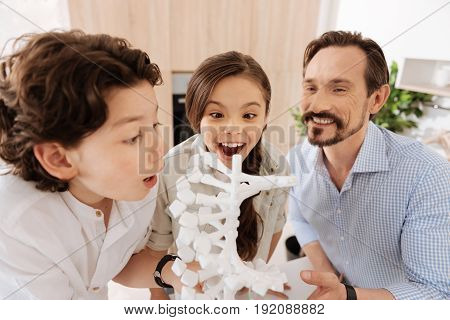 Happy faces. Cute little children and their pleasant young father standing around a white 3D DNA model and scrutinizing a novelty with overjoyed and excited expressions on their faces