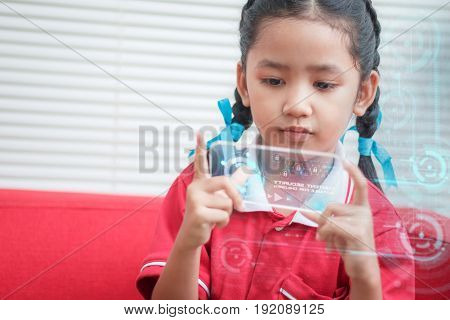 Asian little girl using mobile smart phone with HUD head up display element technology futuristic concept with copy space