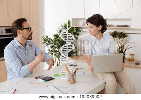 Sonly respect. Handsome dark-haired boy sitting on the kitchen counter with a laptop on his lap and paying attention to every word his father saying