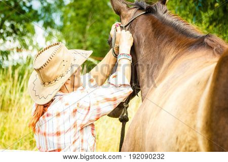 Taking care of animals horsemanship equine concept. Cowgirl getting horse ready for ride on countryside.