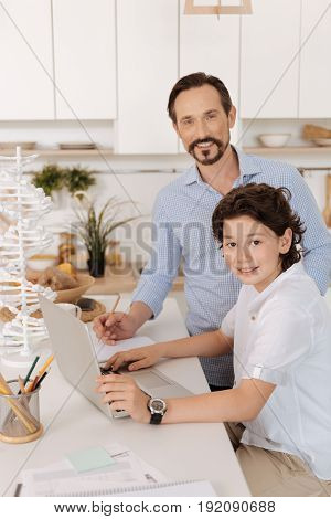 Helping hand. Charming smart teen sitting at the kitchen counter next to his father and holding his hands on the laptop keyboard while his father looking at the camera and being about to make notes