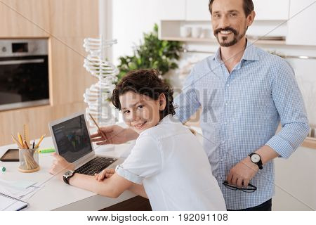 Grateful student. Upbeat bearded man posing near the laptop and being about to explain his son some geography while his son sitting half-turned and smiling at the camera