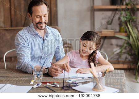 Inspiration vibes. Happy loving father sitting next to his sweet little daughter and helping her to paint a blue sky with watercolors while they both looking inspired