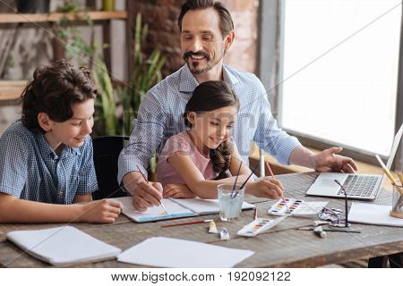 United by art. Pleasant smiling boy watching his father applying strokes on the watercolor painting while his little sister picking new color