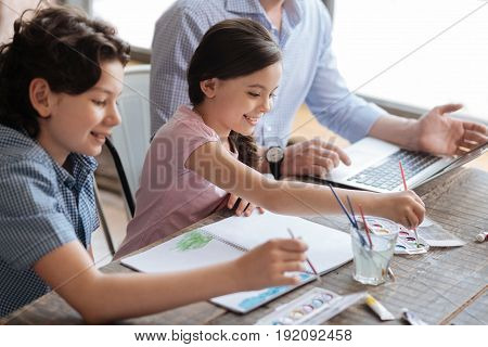 Art is bonding. Pleasant happy children sitting at the table and painting a watercolor picture together while their father working on the laptop