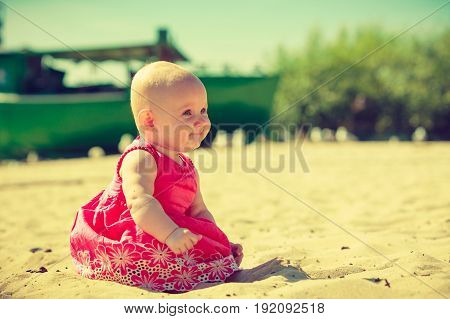 Little Baby Sitting And Playing On Beach