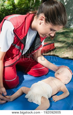 Checking Vital Functions On Infant Dummy Outdoors, Color Image, One Woman Only