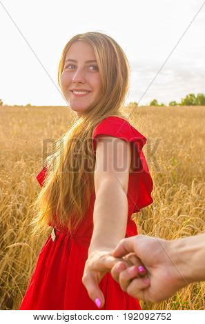 Follow me, Beautiful romantic young woman holds the hand of a man in a wheat field.