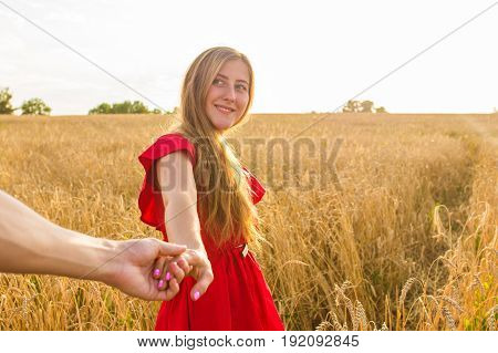 Follow me, Beautiful sexy young woman holds the hand of a man in a wheat field.