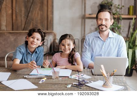 Happiest family. Lovely happy family sitting at the table in a line and smiling at the camera with kids painting a watercolor picture and father doing some work on his laptop