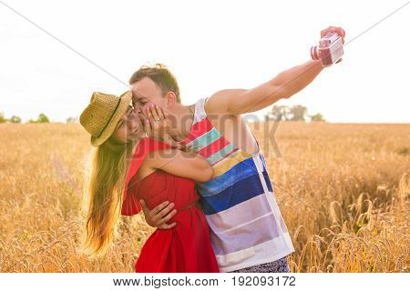 Young happy couple taking a selfie in the field.