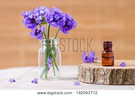lavender essential oil in a brown bottle and fresh lavender flowers for relax selective focus