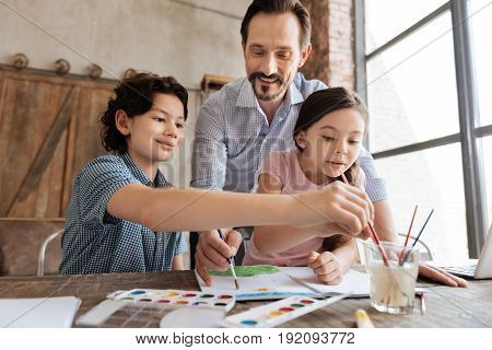 Absolutely involved. Inspired happy family being concentrated on painting one watercolor picture together with children washing brushes and dad applying strokes